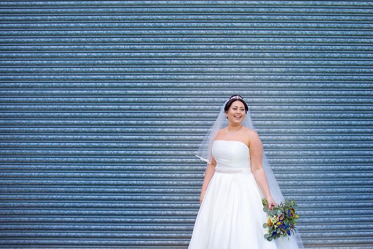 Bride posing by metal door.
