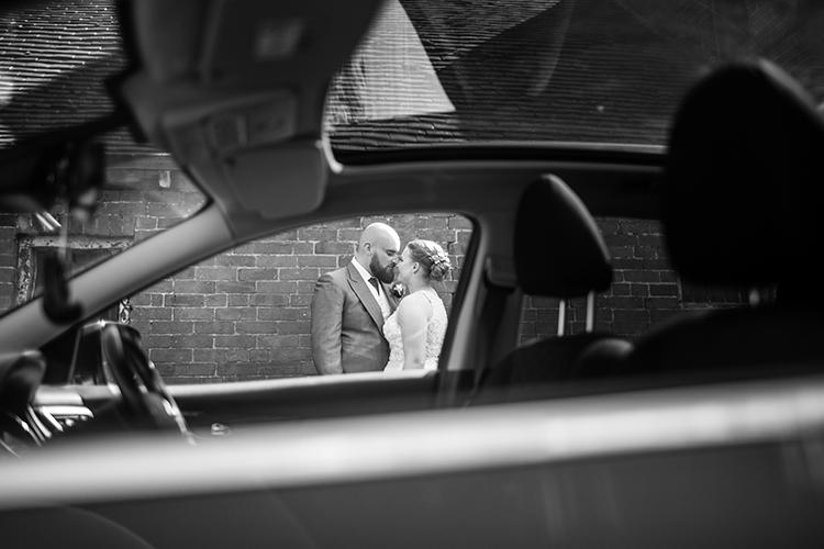 The Bride and Groom shot through a car.