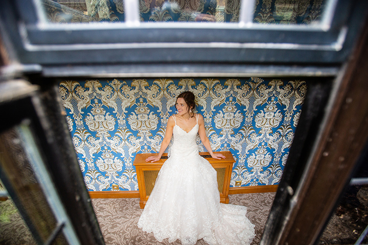 Bride photographed through window.