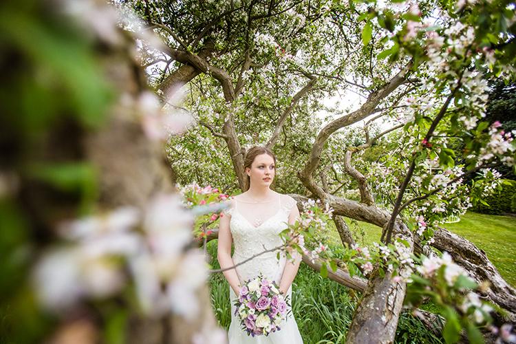 Bride posing next to the tree at Bordesley park