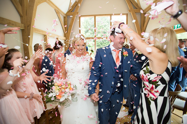 bride and groom walking down the isle with confetti being thrown