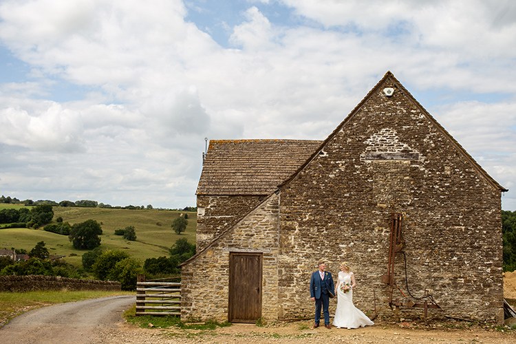 bride and groom by a cottage