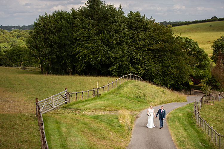 bride and groom walking up the lane