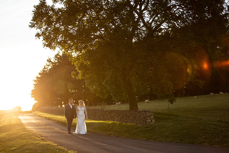 wedding couple walking down a lane