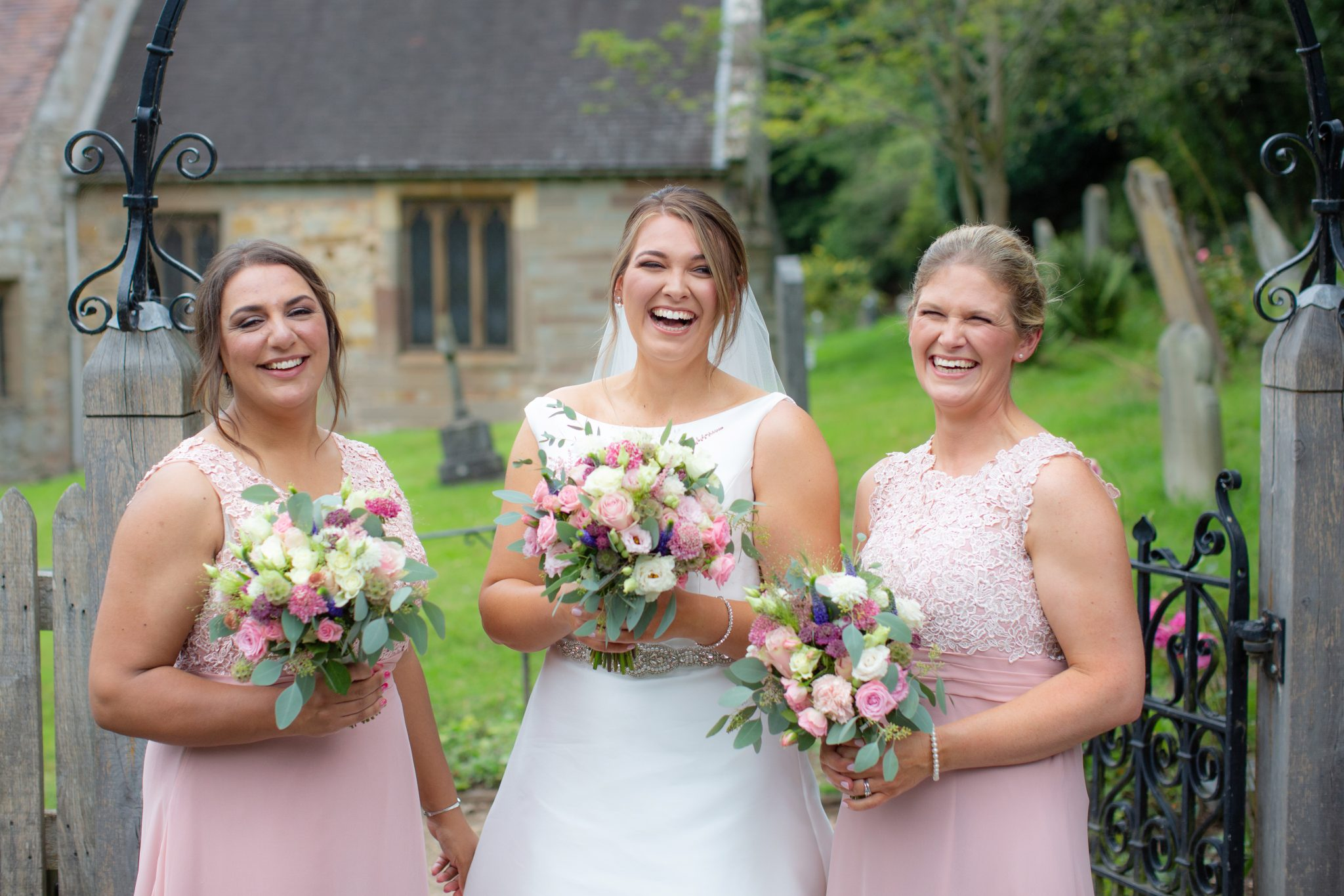 Bride and bridesmaids laughing.