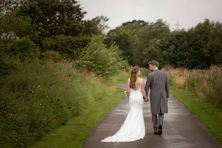 Bride and Groom walking down drive.