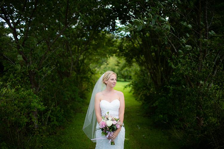 Bride posing in tree arch.