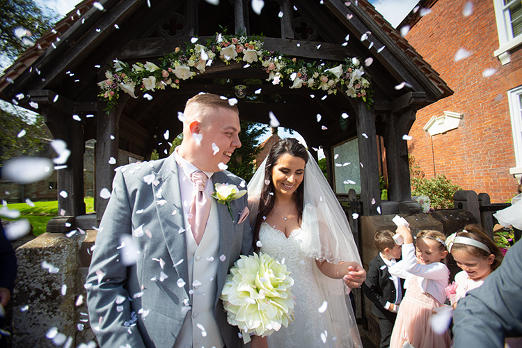 Bride and Groom walking through confetti..